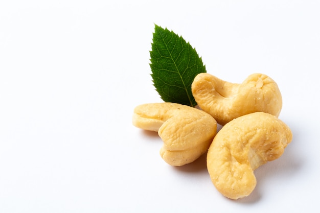 Cashew nuts with a green leaf on white background