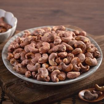 Орехи кешью с кожурой в тарелке на деревянном подносе