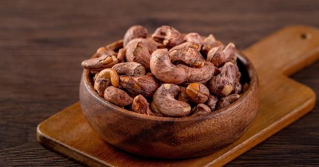 Орехи кешью с кожурой в деревянной миске на деревянном столе