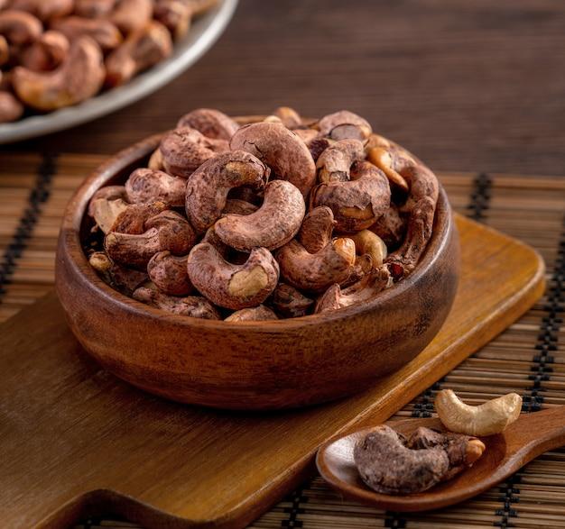 Орехи кешью с кожурой в деревянной миске на деревянном