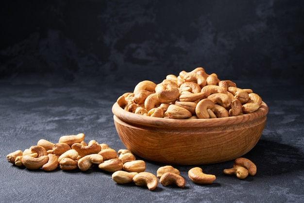 Cashew nuts in wooden bowl on black, close-up