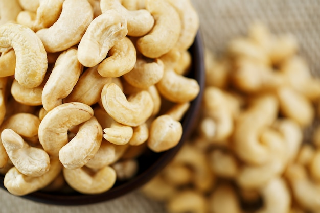 Cashew nuts in a wooden bowl on a burlap cloth background