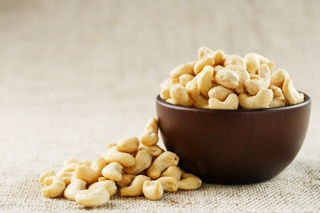 Cashew nuts in a wooden bowl on a burlap cloth .