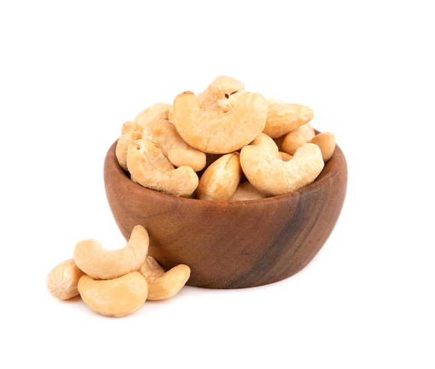 Cashew nuts in wooden bowl, isolated on white background. roasted cashew nuts.