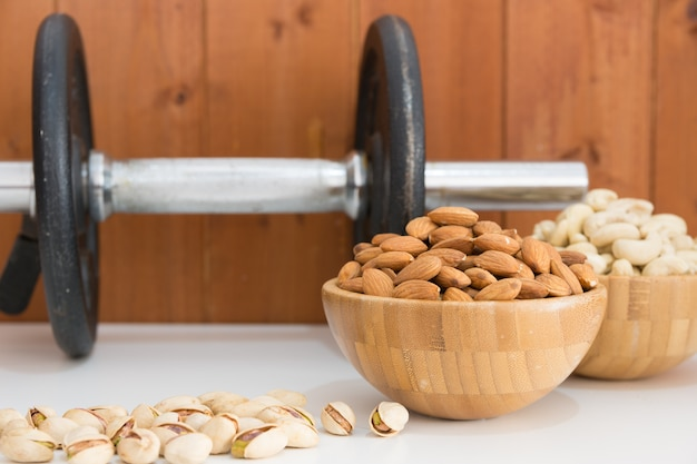Cashews and almonds with a dumbbell behind