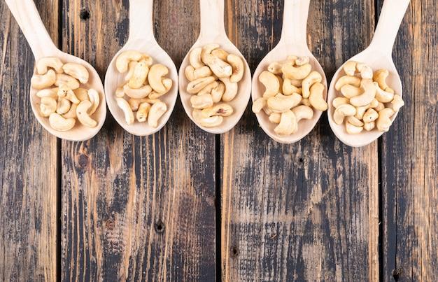 木製のテーブルの上に木製のスプーントップビューでカシューナッツ