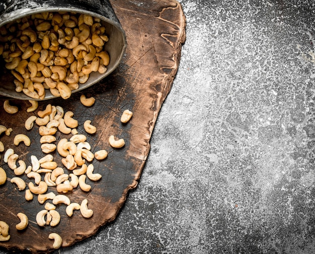 Cashews in the old bucket. on rustic background.