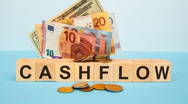 Слово денежного потока, написанное на лесных кубиках
