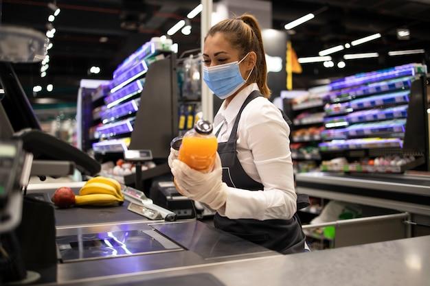 코로나 바이러스로부터 완전히 보호되는 마스크와 장갑을 착용 한 슈퍼마켓의 계산원