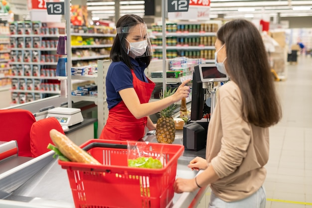 Cashier and customer wearing personal protective masks in modern supermarket during quarantine days