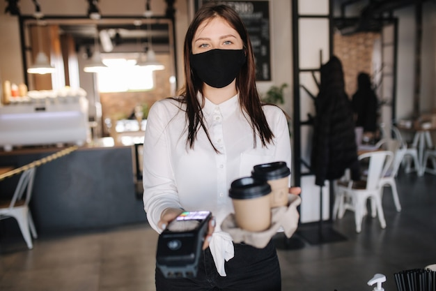 Cashier in face mask holding credit card reader machine and two cups of coffee contactless payments