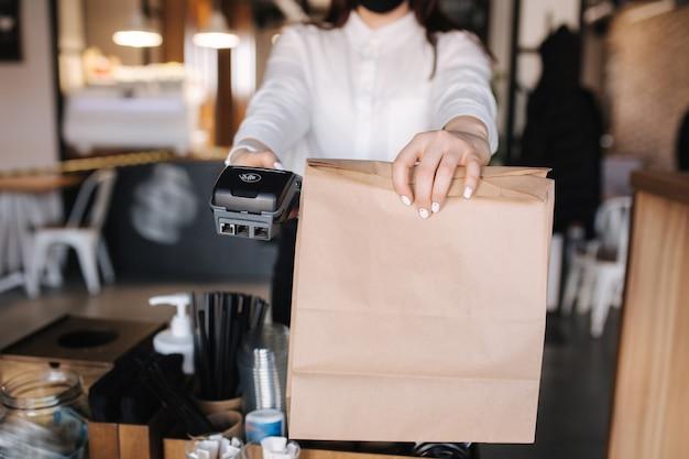 Рука кассира, держащая устройство для чтения кредитных карт и упаковку с концепцией бесконтактных платежей за еду