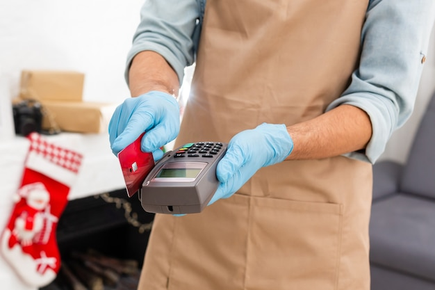 신용카드 판독기를 들고 일회용 장갑을 끼고 코비드-19 전염병 동안 스마트폰으로 결제하는 계산원.