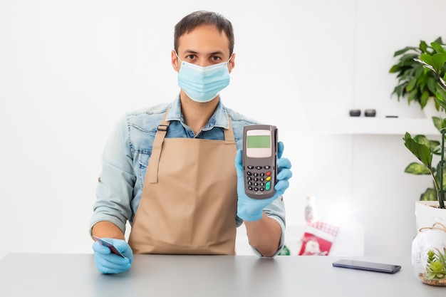 Cashier hand holding credit card reader machine and wearing disposable gloves, paying with smartphone during covid-19 pandemic.