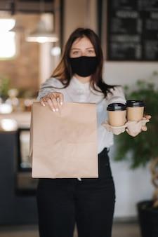 Кассир в маске, держащей пакет с едой и двумя чашками кофе, концепция бесконтактных платежей