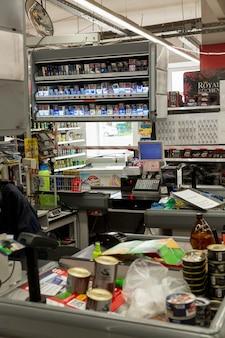 Рабочее место кассира в супермаркете. полки с продуктами и сигаретами. вертикальный. москва, россия, 02.07.2021.