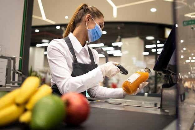 Cassiere in un supermercato che indossa maschera e guanti completamente protetti contro il virus corona