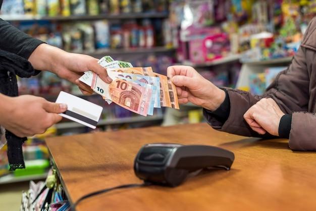 계산원은 소비자 손에서 유로 지폐를