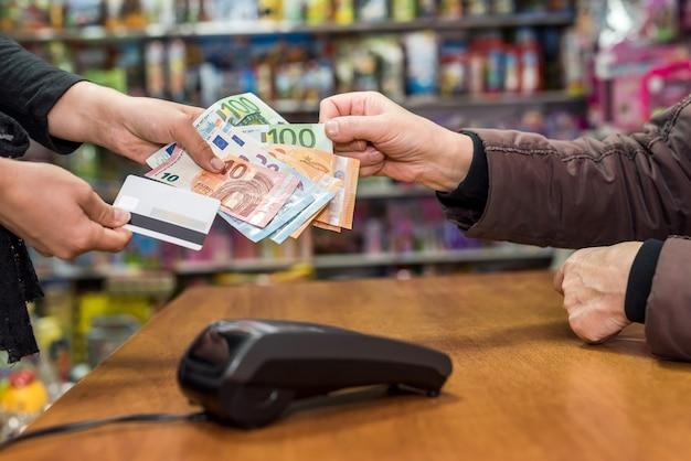 계산원은 소비자 손에서 유로 지폐를 가지고