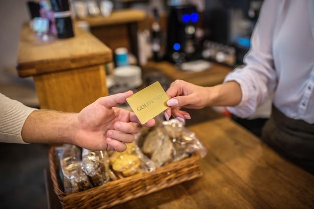 顧客からカードを受け取るレジ係