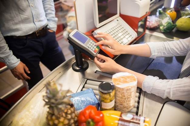 Cashier using payment terminal in supermarket