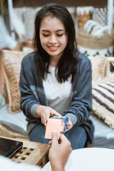 レジ係の女性は、工芸品店のオンライン支払い施設として電子データキャプチャマシンを使用しています