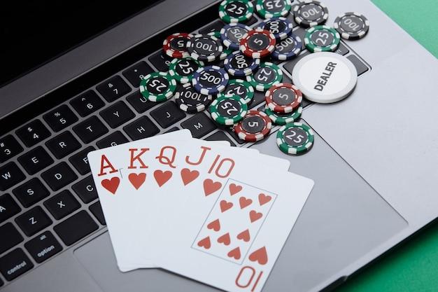 ラップトップに積み重ねられたカジノチップとカード。オンラインカジノのコンセプト。