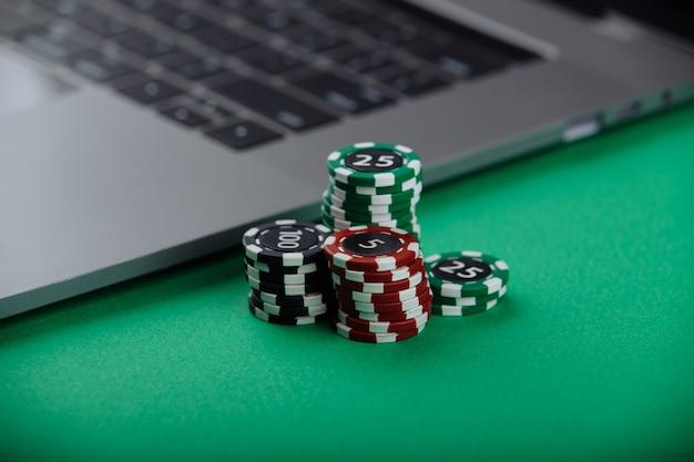 緑の背景にカジノチップとラップトップ。カジノのオンラインコンセプト。
