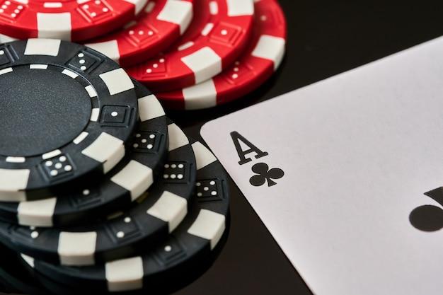 Фишки казино и игральные карты на темном отражающем фоне