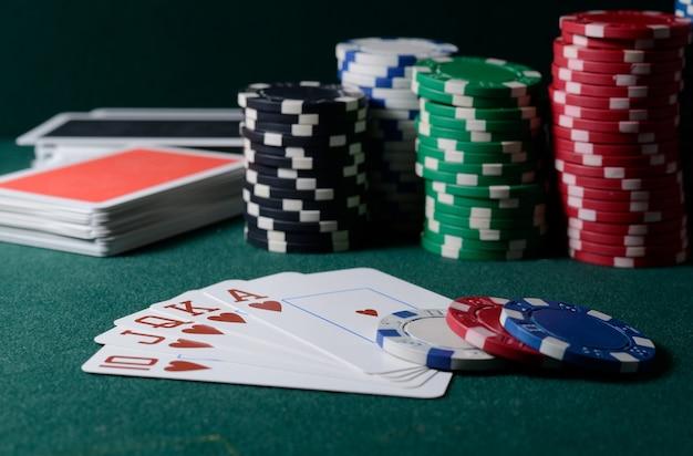 녹색 테이블에 카지노 칩과 로얄 플러시 카드 조합. 포커 게임 테마