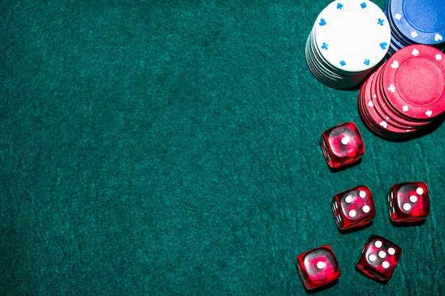 Casino chips and dice on green table
