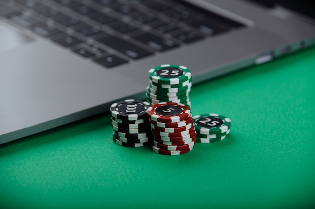 Casino chips and laptop on green background. casino online concept.