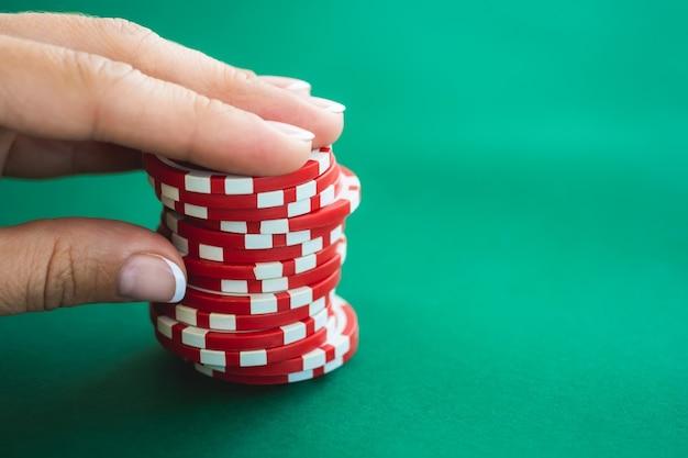 Фишки казино на покерном столе в руках игрока