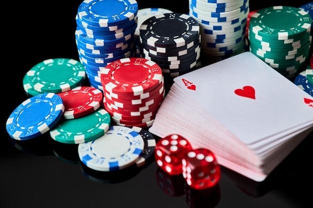 Фишки казино, игральные карты и кубики на темном отражающем фоне