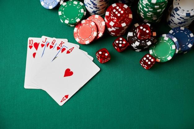 Фишки казино, игральные карты и кости на столе из зеленой ткани