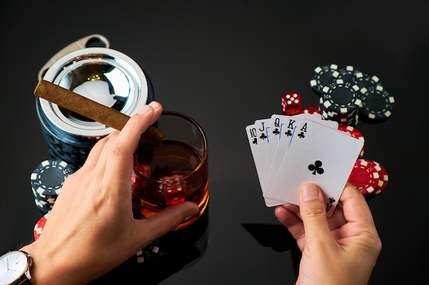 Casino chips playing cards glass of whiskey and dices on dark reflective background