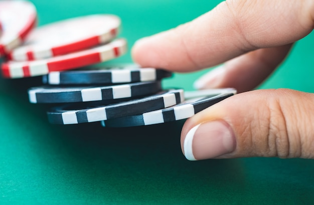Casino chips on poker table held by gamer hand