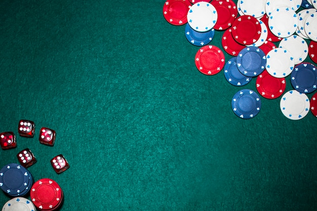 Casino chips and red dices on green poker backdrop