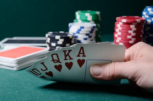Casino chips and royal flush cards combination on the green table. poker game theme