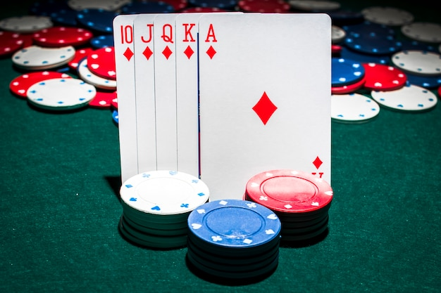 Casino chips stack in front of royal flush playing card