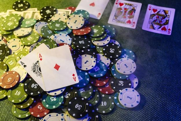Концепция казино: игральные карты, фишки для ставок и деньги. вид сверху. дым добавлен к фото