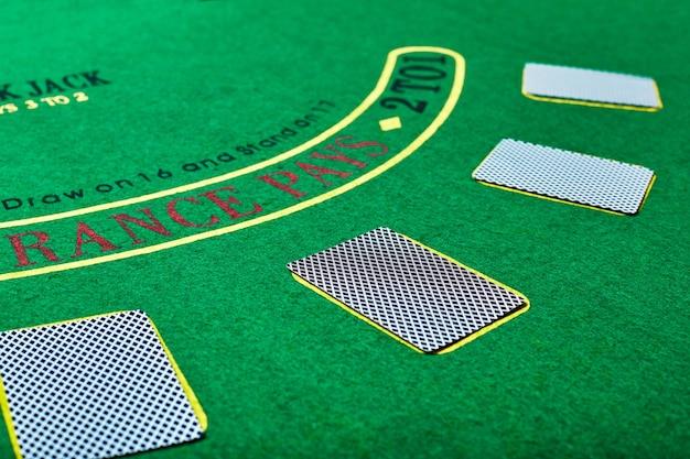 Концепция казино, азартных игр, покера и развлечений - игральные карты на зеленой поверхности стола