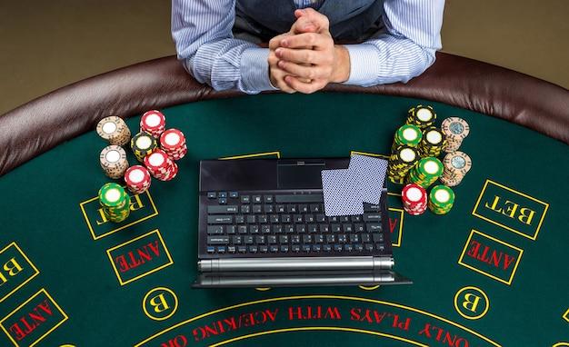 Казино, азартные игры онлайн, технология и люди концепция - крупный план игрока в покер с игральными картами, ноутбуком и фишками за зеленым столом казино