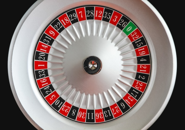 黒い表面で隔離されるカジノのルーレットの車輪