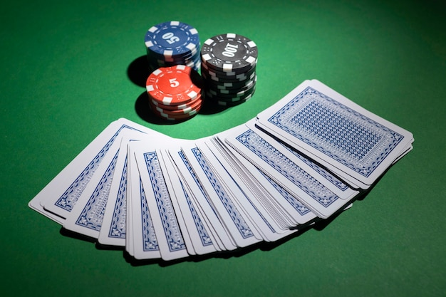 Casino tokens on green background with deck of cards