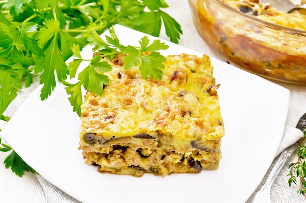 Casserole of minced meat, onion and eggplant, sauce of eggs, milk, cheesein plate against board