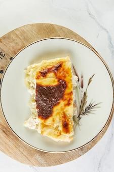 明るい背景のプレートにチーズとスイバのキャセロールパイ。