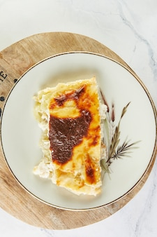 Casserole pie with cheese and sorrel on plate on light background.