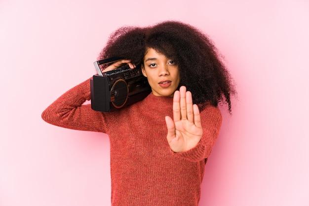 一時停止の標識を示す差し出された手で立っているcasseteを保持している若いアフロ女性