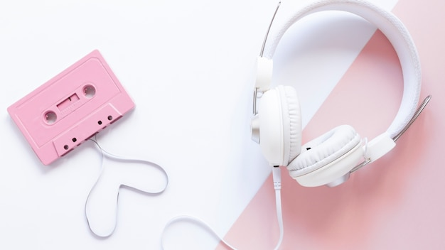 Cassette and earphones on white and pink background